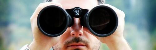 hombre mirando a través de prismáticos recortada