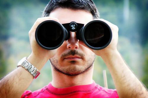 hombre mirando a través de prismáticos