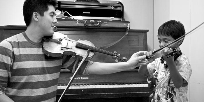Profesor particular de violín enseñando a un niño